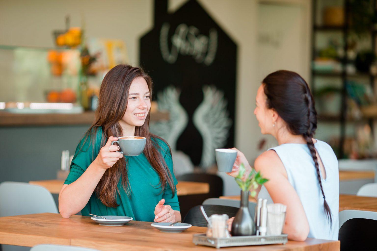 2 cô gái trẻ vừa uống cafe vừa trò chuyện trong nụ cười